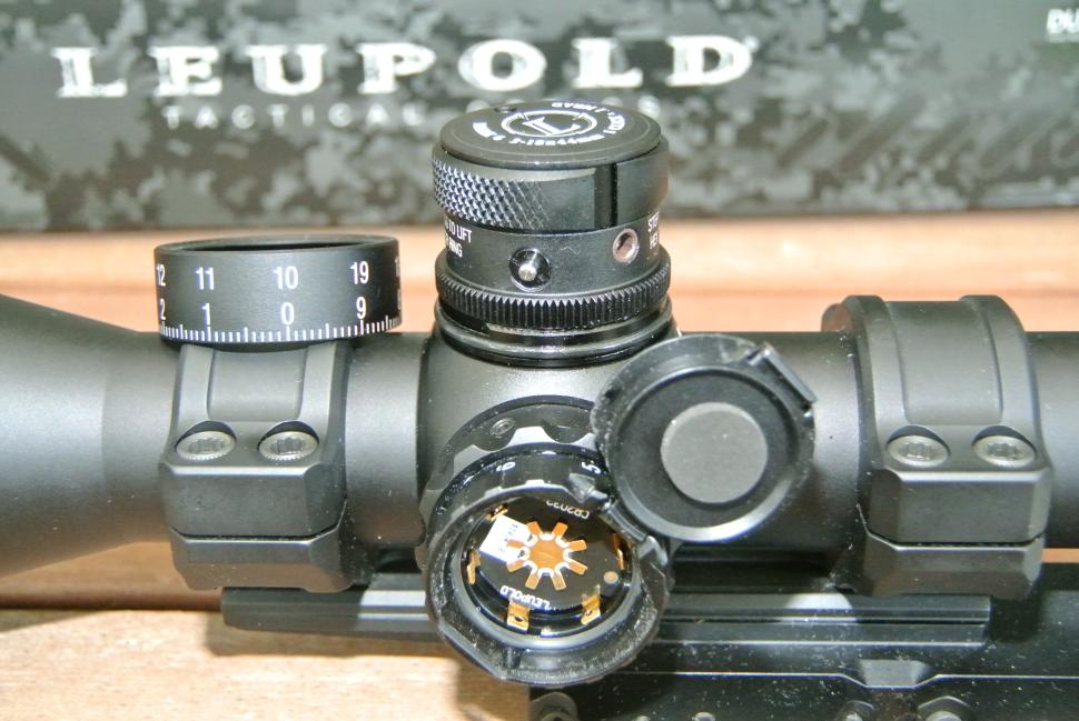 Leupold Mark 6 3-18x showing M5B2 elevation knob with scale removed and hinged illumination battery door open